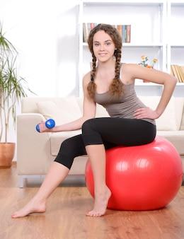 Retrato da mulher bonita nova com bola da aptidão em casa.