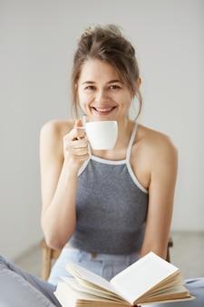Retrato da mulher bonita nova feliz que sorri hoding a xícara de café e o livro que sentam-se no assoalho sobre a parede branca.