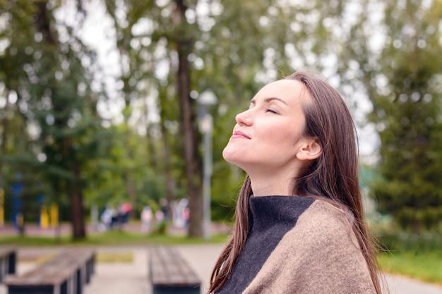 Retrato da mulher bonita nova que faz a respiração do ar fresco do outono em um parque verde.