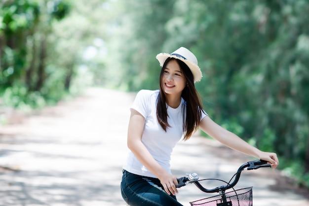 Retrato da mulher bonita nova que monta uma bicicleta em um parque.
