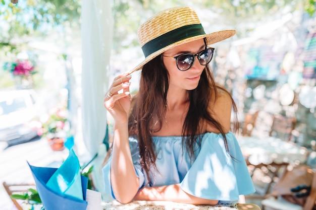 Retrato da mulher bonita nova que senta-se em um café bebendo ao ar livre do café.