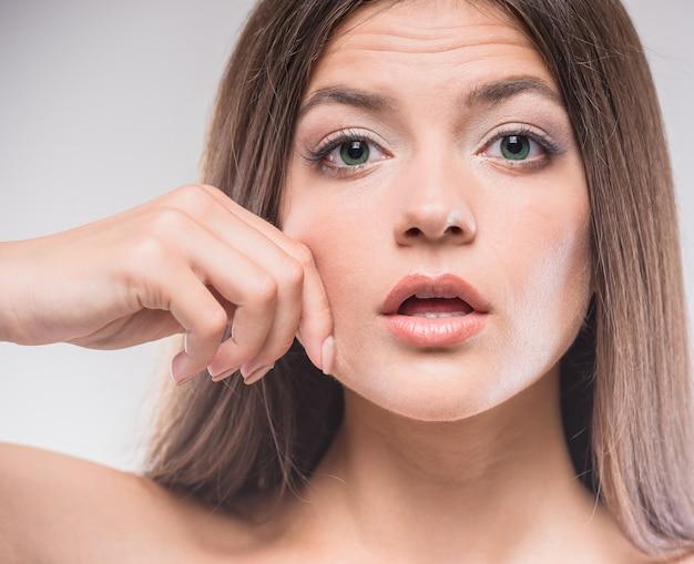 Retrato da mulher bonita que comprime a pele em seu mordente.