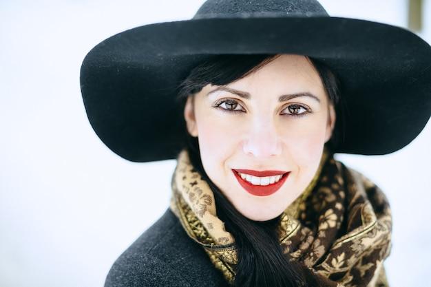 Retrato da mulher bonita que está e que sorri no chapéu preto e no revestimento e que olha feliz durante o dia.