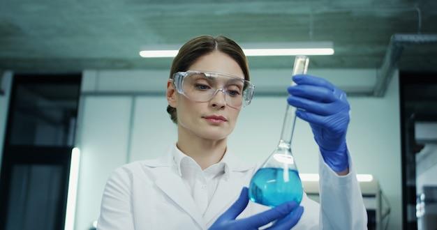 Retrato da mulher caucasiana de óculos e roupão branco, fazendo uma análise do líquido azul no tubo de ensaio durante pesquisas médicas ou farmacêuticas e em laboratório.