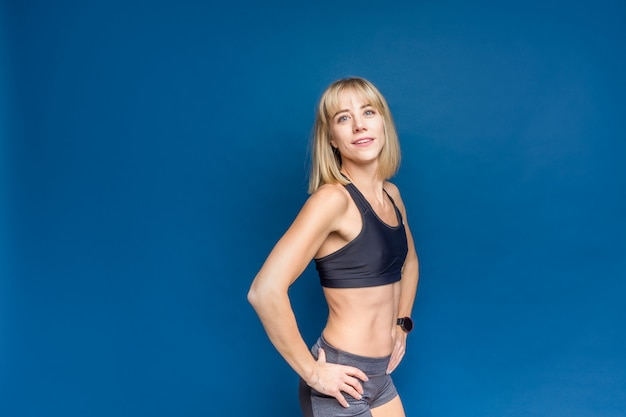 Retrato da mulher caucasiano atlética bonita no sutiã e no short do esporte em um espaço azul do estúdio. copyspace