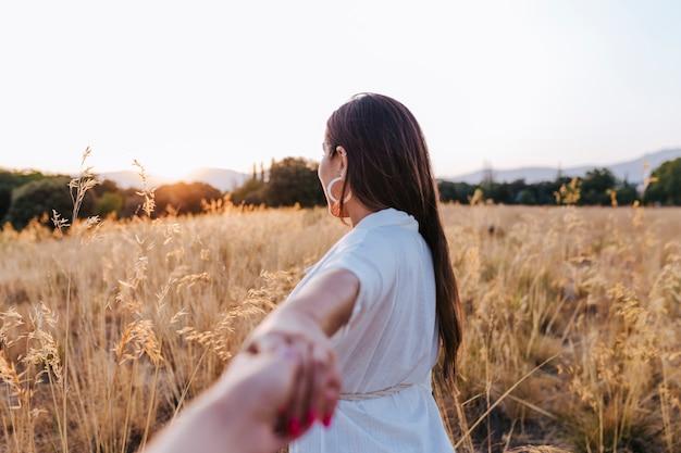 Retrato da mulher caucasiano bonita nova ao ar livre no por do sol em um campo amarelo. usando um chapéu moderno e sorrindo. de mãos dadas, siga-me conceito