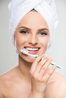 Retrato da mulher com a toalha na cabeça usando a escova de dentes.