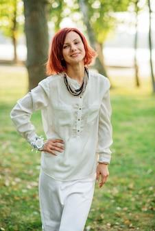 Retrato da mulher de cabelo vermelha que veste no vestido branco contra o parque no partido de galinha.
