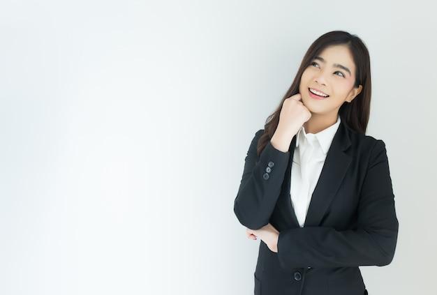 Retrato da mulher de negócio asiática nova que pensa sobre o fundo branco.