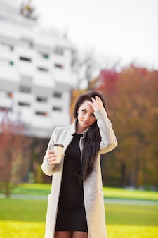 Retrato da mulher de negócio da autoconfiança com café a ir ao lado do escritório.