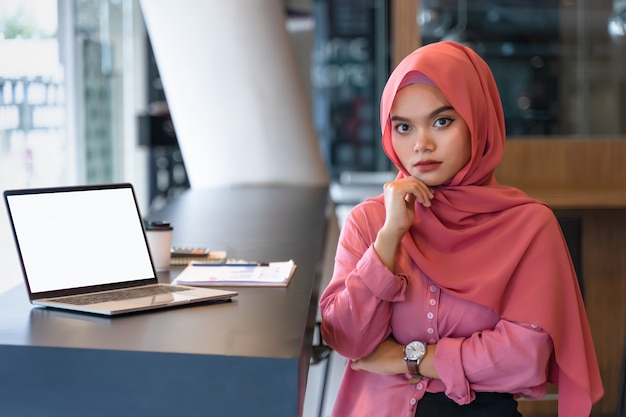 Retrato da mulher de negócio muçulmana nova segura que veste o hijab cor-de-rosa no espaço do trabalho em equipe.