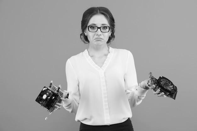 Retrato da mulher de negócio nova confusa confusa bonita confundida com peças do computador do equipamento em preto e branco