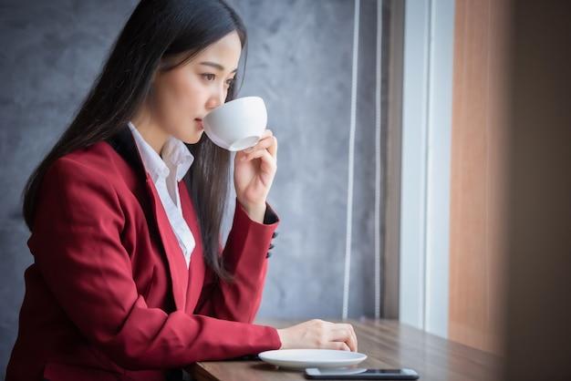 Retrato da mulher de negócios asiática nova que senta-se dentro de casa no café que bebe o café com telefone esperto. conceito de sucesso do negócio.