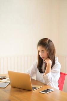 Retrato da mulher de negócios asiática que usa o laptop no escritório moderno.
