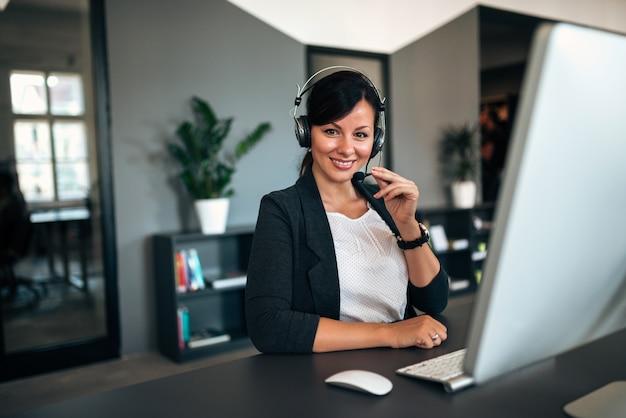Retrato da mulher de negócios bonita que trabalha com auriculares como um apoio ao cliente, olhando a câmera.