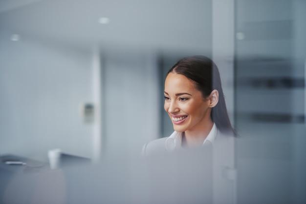 Retrato da mulher de negócios lindo com sorriso toothy grande que está no escritório. foto tirada do lobby. sucesso é a melhor motivação.