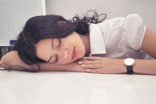 Retrato da mulher de negócios nova inquieta que sente a falta de sono e que dorme na mesa do trabalho.