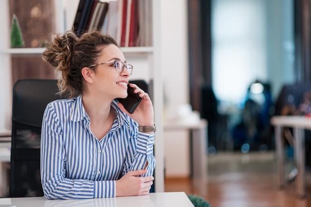 Retrato da mulher de negócios nova que fala no telefone esperto dentro.