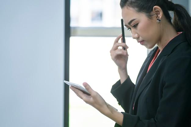 Retrato da mulher de negócios nova segura do empresário que trabalha com tabuleta ou dispositivo móvel na estação de trabalho.