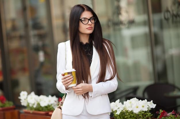 Retrato da mulher de negócios profissional financeira que guarda à disposição uma xícara de café ao caminhar à convenção financeira ao centro de negócios.