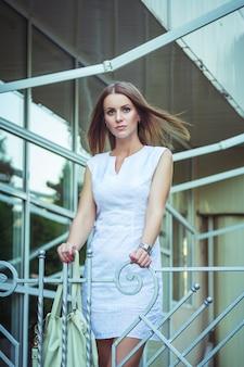 Retrato da mulher de negócios triste e séria nova bonita, estando a construção próxima. estilo de rua urbana de verão.