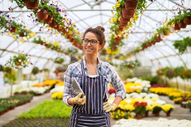 Retrato da mulher de sorriso bonita da florista da idade média que está na estufa grande com uma tabuleta à disposicão e que olha longe.