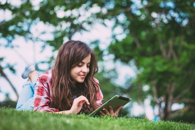 Retrato da mulher de sorriso bonita nova com pc da tabuleta, ao ar livre.