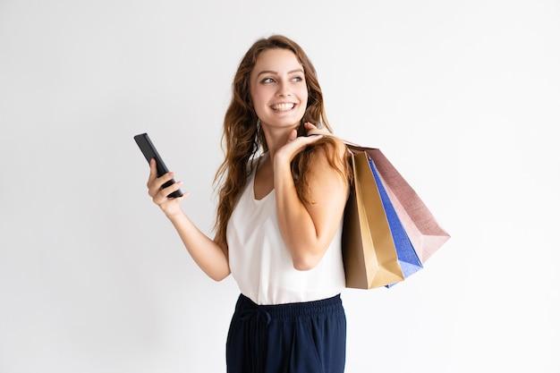 Retrato da mulher de sorriso com sacos de compras e smartphone.