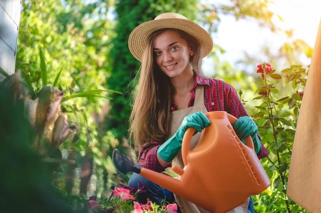 Retrato da mulher de sorriso feliz do jardineiro no chapéu e no avental com a lata molhando no jardim home. jardinagem e floricultura