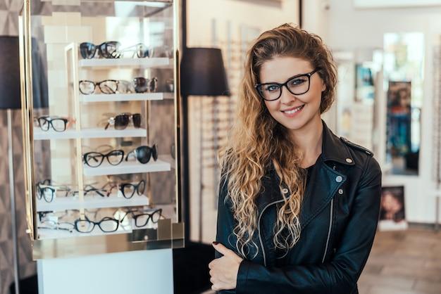 Retrato da mulher de sorriso na loja ótica.