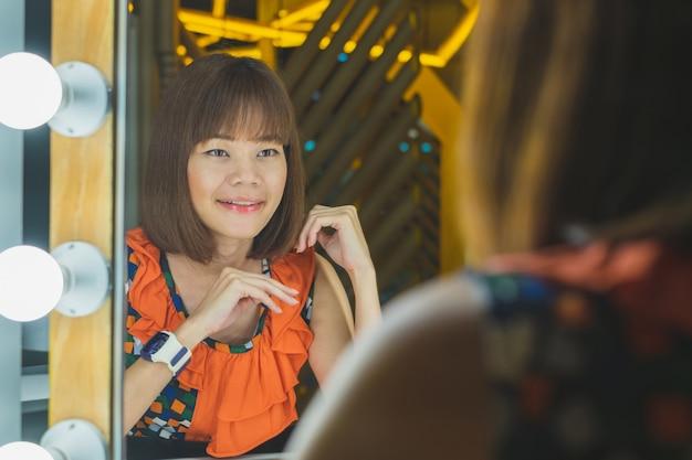 Retrato da mulher de sorriso nova que olha o espelho na tabela de pingamento.