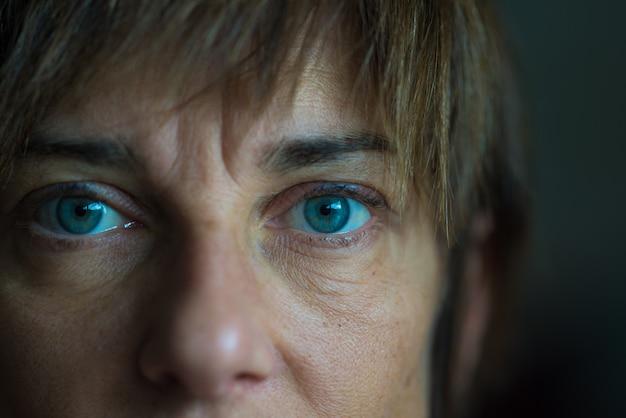 Retrato da mulher envelhecida meados de com olhos azuis, fim acima e foco seletivo em um olho, profundidade de campo muito rasa. configuração escura, imagem enfraquecida.