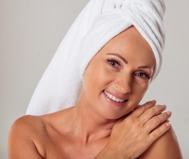 Retrato da mulher envelhecida média bonita com uma toalha.