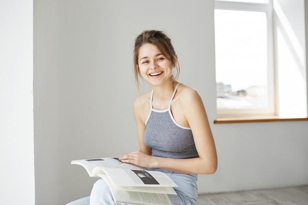 Retrato da mulher feliz bonita nova que sorri rindo guardando o livro que senta-se na cadeira sobre a parede branca em casa.