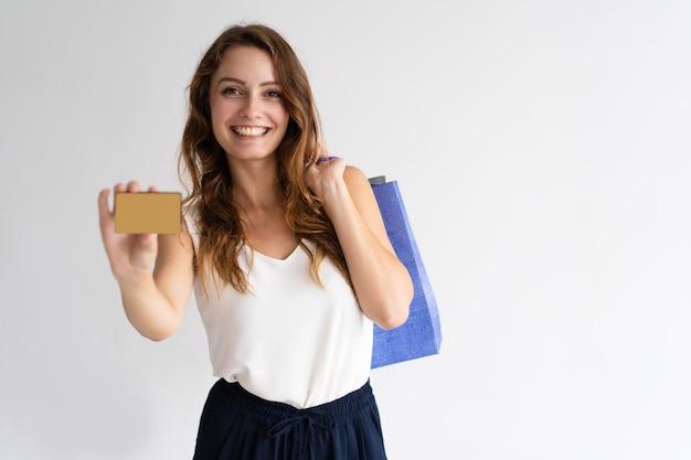 Retrato da mulher feliz com os sacos de compras que mostram o cartão de crédito.