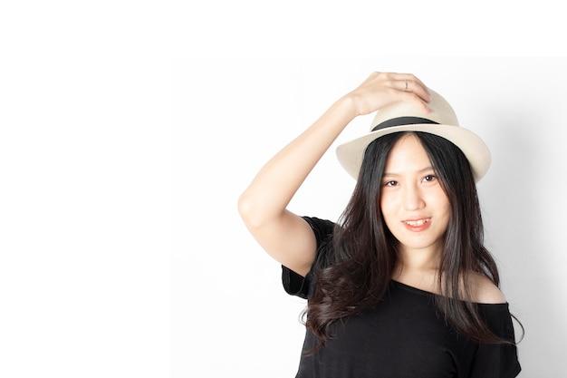 Retrato da mulher feliz no chapéu com o sorriso olhando a câmera isolada no fundo branco.