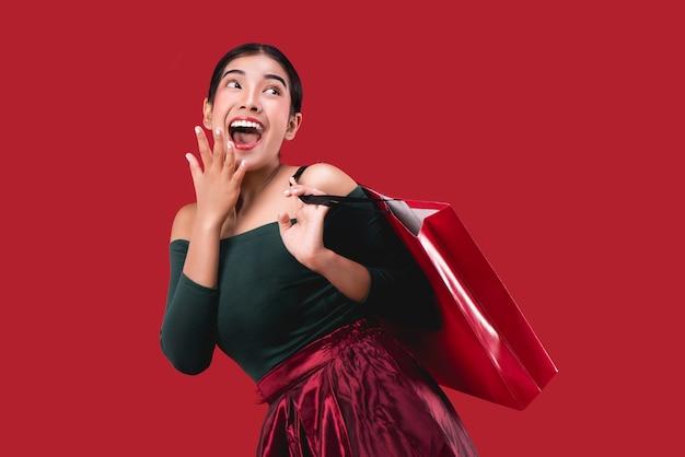 Retrato da mulher feliz nova feliz que levanta com os sacos de compras sobre o fundo vermelho.