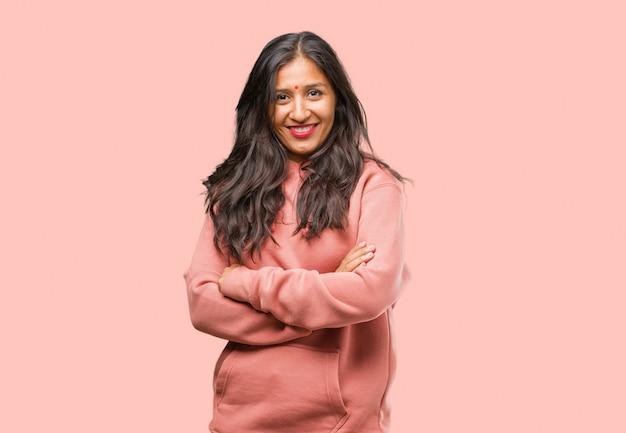 Retrato da mulher indiana nova da aptidão que cruza seus braços, sorrindo e felizes, sendo confiáveis e amigáveis