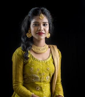 Retrato da mulher indiana tradicional bonita que levanta na parede preta.