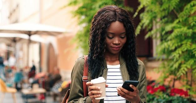 Retrato da mulher jovem e atraente multirracial falando smartphone e bebendo café ao ar livre b.