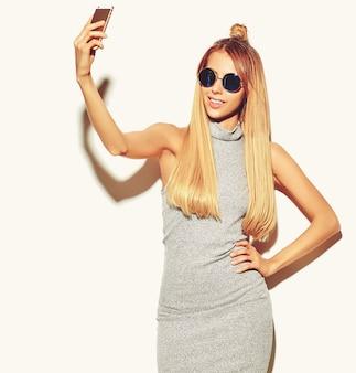Retrato da mulher loira bonita sorridente feliz bonita em roupas de verão casual hipster cinza sem maquiagem isolada no branco tomando uma selfie