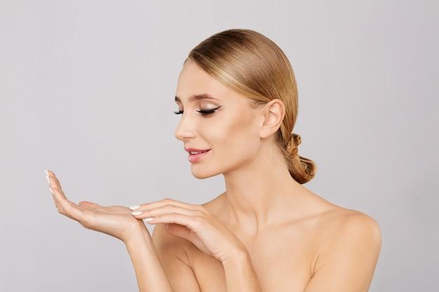 Retrato da mulher loira bonita sorridente, mostrando o espaço vazio da cópia na palma da mão aberta.