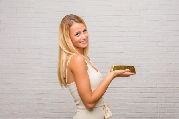 Retrato da mulher loura bonita nova contra uma parede de tijolos que guarda algo com as mãos, mostrando um produto, sorrindo e alegre, oferecendo um objeto imaginário. segurando um lingote de ouro.