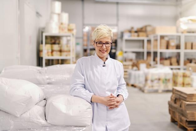 Retrato da mulher loura caucasiano loura nova de sorriso no uniforme estéril e nos óculos que inclinam-se em sacos da farinha na fábrica de alimentos.