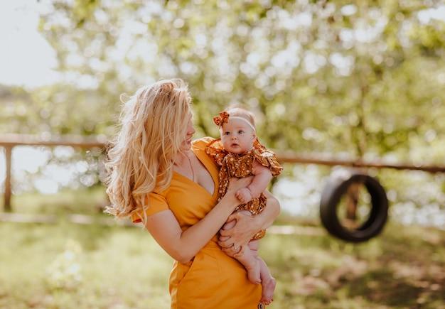 Retrato da mulher loura consideravelmente nova no vestido amarelo do verão com bebê. arco de cabelo