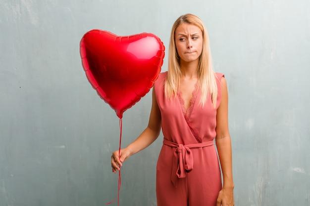 Retrato da mulher loura elegante nova que duvida e confuso, pensando de uma ideia ou preocupado com algo. segurando um balão de coração vermelho.