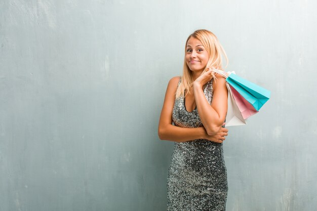 Retrato da mulher loura elegante nova que duvida e que shrugging os ombros, conceito da indecisão e insegurança, incertos sobre algo. segurando a sacola de compras.