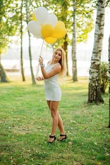Retrato da mulher loura que veste no vestido branco com os balões nas mãos contra o parque no partido de galinha.