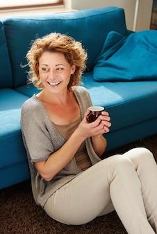 Retrato da mulher mais idosa feliz em casa que guardara a caneca de café