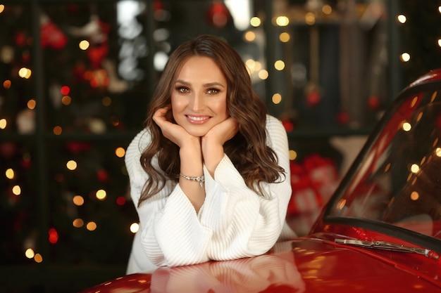 Retrato da mulher modelo fofo com largo sorriso e penteado elegante com luzes de natal festivas em segundo plano.